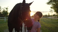 CLOSE UP: Smiling young girl petting beautiful big brown horse at golden sunset Stock Footage