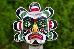 A weathered sun mask totem at a burial ground in Alert Bay on Cormorant Island Stock Photos