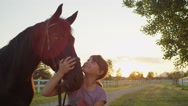 CLOSE UP: Cute cheerful little girl kissing beautiful big brown horse at sunset Stock Footage