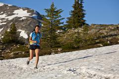A young asian woman trailrunning across snow in the Trophy Mountains, Wells Grey Stock Photos