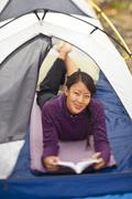 A happy, healthy woman does some reading while camping in Jasper National Park, Stock Photos