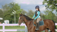 SLOW MOTION: Brave happy little girl horseback riding big strong brown horse Stock Footage