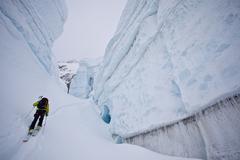 A woman backcountry ski touring through incredible glacier ice. Icefall Lodge, Stock Photos
