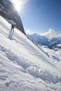 A male ski mountaineer bootpacks up a steep exposed slope. Icefall Lodge, Stock Photos