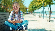 Portrait school girl 7-8 years in sunglasses using smartphone sitting on bench Stock Footage