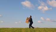 Businessman carries the box Stock Footage