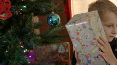 Happy boy looking for presents under the new year tree Stock Footage