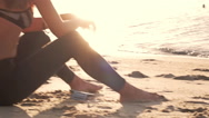 Young sports woman sit on the beach Stock Footage