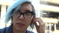 Transgender Gay with blue Hair sitting listening to music through headphones Stock Footage