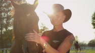 CLOSE UP: Portrait of smiling senior cowboy petting his horse and saying hello Stock Footage