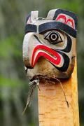 A weathered totem of an eagle head at a burial ground in Alert Bay on Cormorant Stock Photos