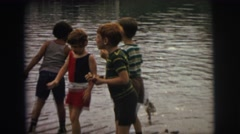 1974: a group of children on a dock, some are feeding ducks  Stock Footage