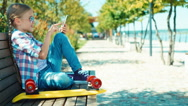 Portrait school girl 7-8 years using smartphone and sitting on the bench Stock Footage