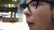 Transgender Gay with blue Hair eating green Apple while sitting at the Mall Stock Footage