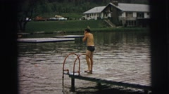 1974: a boy in swimming trunks preparing to dive off a wooden dock  Stock Footage