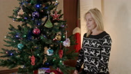 Mother sitting under the Christmas tree with toys and admires Stock Footage
