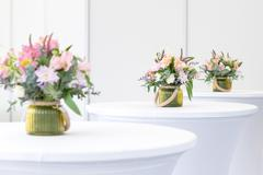 Beautiful flower arrangement on white festive tables Stock Photos