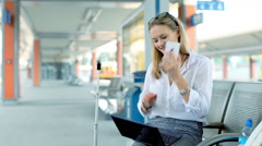 Businesswoman talking on cellphone and working on laptop while sitting on platfo Stock Footage