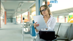 Businesswoman writing something on documents while sitting on the train station Stock Footage