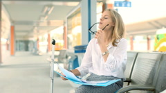 Busy businesswoman reading documents while sitting on the train station Stock Footage