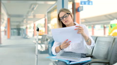 Tired businesswoman checking time while reading documents on the train station Stock Footage