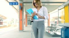 Businesswoman standing on the train station and reading documents, steadycam sho Stock Footage