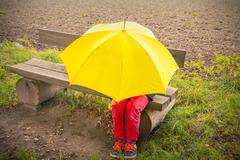 Teenage boy on a bench hidden by a yellow umbrella Stock Photos