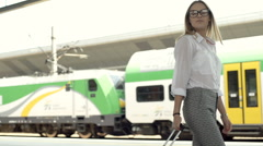 Businesswoman walking with suitcase on the train station, steadycam shot Stock Footage