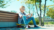 Girl in sunglasses using her smartphone sitting on the skateboard near bench Stock Footage