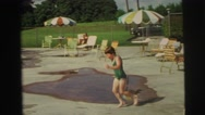1974: the kid jump into the swimming pool and swims and enjoying LYNBROOK Stock Footage