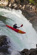 A female kayaker paddles over Overlander Falls. Fraser River, Mt Robson Stock Photos