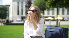 Happy businesswoman spending her break outdoors and drinking coffee Stock Footage