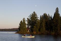 Couple paddle canoe on Source Lake, Algonquin Park, Ontario, Canada. Stock Photos