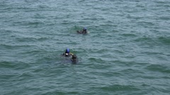 Three scuba divers after immersion in the water view from the drone Stock Footage
