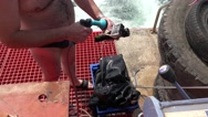 Diver cleans their equipment with fresh water at stern of ship Stock Footage