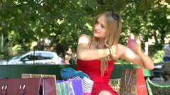 Pretty, stylish girl brushing her hair while sitting in the park Stock Footage