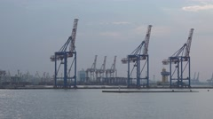 Commercial seaport with cranes on horizon in morning mist Stock Footage