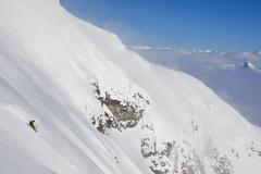 A male backcountry snowboarder rides a steep face on Mt Cartier, Revelstoke, BC Stock Photos