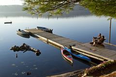 Middle-aged couple enjoy quiet morning on dock near their cottage, Source Lake, Stock Photos