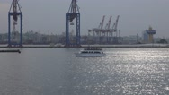 Passenger boat passes by commercial sea port in morning mist Stock Footage