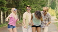 Cheerful friends dancing and waving hands at concert in park, summer weekend Footage