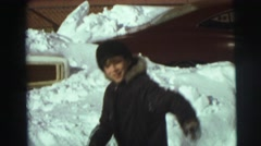 1974: a young boy plays in the snow using a snow shovel. LYNBROOK, NEW YORK Stock Footage