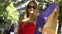 Stylish girl going round and holding shopping bags, slow motion shot at 240fps Stock Footage