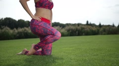 Sporty woman doing hip flexor stretch in the park Stock Footage
