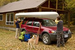 Young couple load canoe on roof of vehicle at cottage near South River, Stock Photos