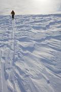 A male ski tourer skins along wind sastrugi, Sol Mountain Lodge, Monashee Stock Photos