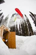 A male backcountry snowboarder airs an outhouse, Icefall Lodge, Canadian Stock Photos