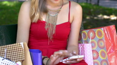 Skinny girl in red dress sitting in the bench and texting on smartphone Stock Footage