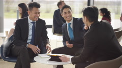 4K Asian businessmen in discussion in busy meeting area of modern office Stock Footage