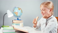 Portrait schoolgirl 7-8 years eating sweet wafer and reading book at the table Stock Footage